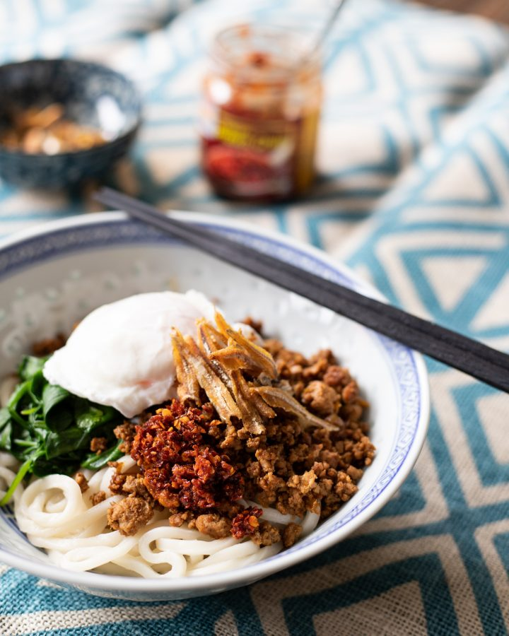 bowl of chilli pan mee noodles with crispy chilli, ikan bilis and poached egg